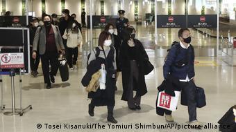 Авиапассажиры в защитных масках в аэропорту Токио