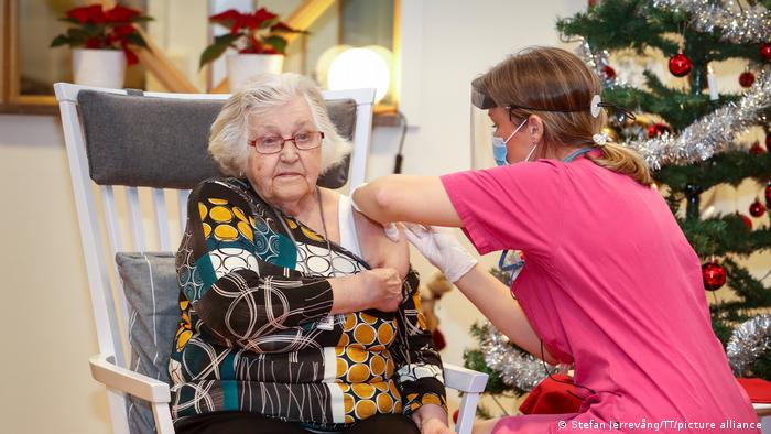An elderly woman receives her vaccine in Sweden