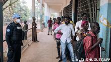 27.12.2020 *** Voters queue to vote as a police officer from the United Nations Multidimensional Integrated Stabilization Mission in the Central African Republic (MINUSCA) looks on at the Barthélemy Boganda high school polling station in the 4th district in Bangui, Central African Republic (CAR), on December 27, 2020 during the country's presidential and legislative elections. - Voting began in the Central African Republic on December 27, 2020, in a key test for one of the world's most troubled nations. The polls take place after a week of turbulence, marked by accusations of an attempted coup, the brief seizure of the CAR's fourth-largest town and the dispatch of military personnel by Russia and Rwanda to help its beleaguered government. (Photo by ALEXIS HUGUET / AFP)