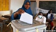 A woman cast her ballot at a polling station in Niamey on December 27, 2020 during Niger's presidential and legislatives elections. - Voters in the Sahel state of Niger go to the polls on December 27, 2020 for an election that could seal the country's first-ever peaceful handover between elected presidents, despite a bloody jihadist insurgency. (Photo by Issouf SANOGO / AFP)