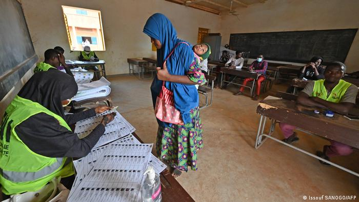 Electoral commission officials checks the voters roll as a woman with a baby on her back prepares to vote at a polling station in Niamey on December 27, 2020 during Niger's presidential and legislatives elections