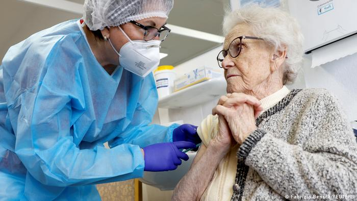 Elderly woman receiving the vaccine, looking at the doctor