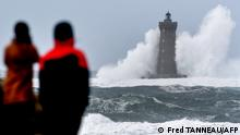 People watch high waves and strong winds hitting The Four Lighthouse (Lighthouse of the Four d'Argenton) at Porspoder, western France on December 27, 2020, as Storm Bella strikes the coast of Britanny. (Photo by Fred TANNEAU / AFP)