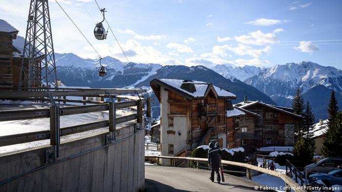 A skiers walk under a ski lift in the Alpine resort of Verbier