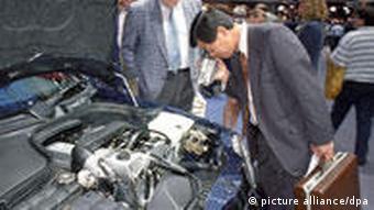 Ein Besucher filmt auf der Internationalen Automobilausstellung IAA einen Motor mit seiner Videokamera (Foto: dpa)