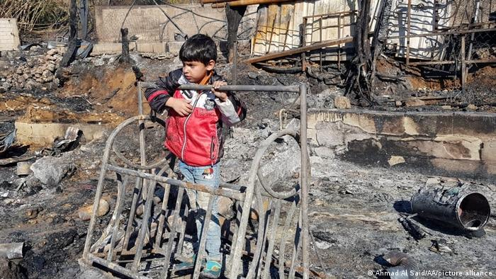 Syrian refugee boy at a burnt-down camp in the north of Lebanon