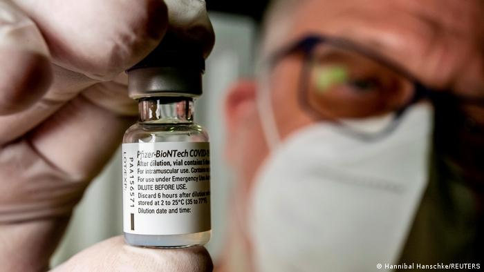 A member of the ASB (Arbeiter-Samariter-Bund) presents a vial with Pfizer-BioNTech COVID-19 vaccine at a vaccination centre in Bad Windsheim, Germany