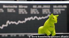Ein kleiner Bulle, Symbol für steigende Kurse, ist am Montag (02.01.2012) am Platz eines Aktienhändlers an der Deutschen Börse in Frankfurt am Main befestigt. Der DAX hatte am Nachmittag die 6000-Punkte-Marke geknackt. Foto: Boris Roessler dpa/lhe ++
