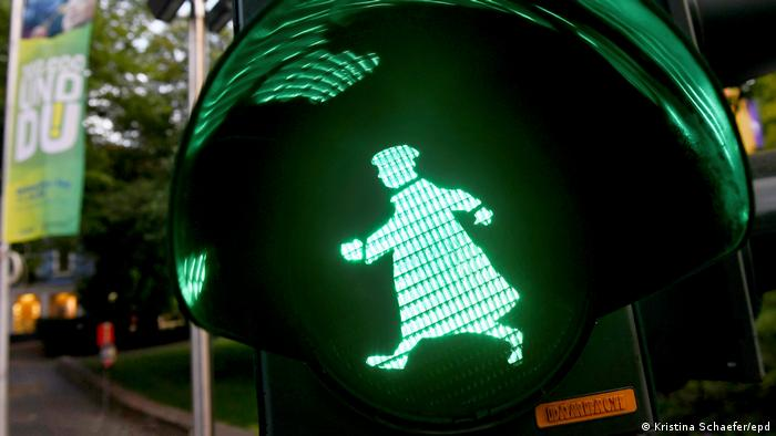 Pedestrian traffic light showing a green walking Luther figure