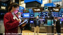 In this photo provided by the New York Stock Exchange, trader Ashley Lara, left, works on the floor during the Golden Falcon IPO, Friday, Dec. 18, 2020. U.S. stock indexes are slipping from their record levels Friday as the wait drags on to see if Congress can reach a deal to send more cash to struggling workers and businesses. (Colin Ziemer/New York Stock Exchange via AP)