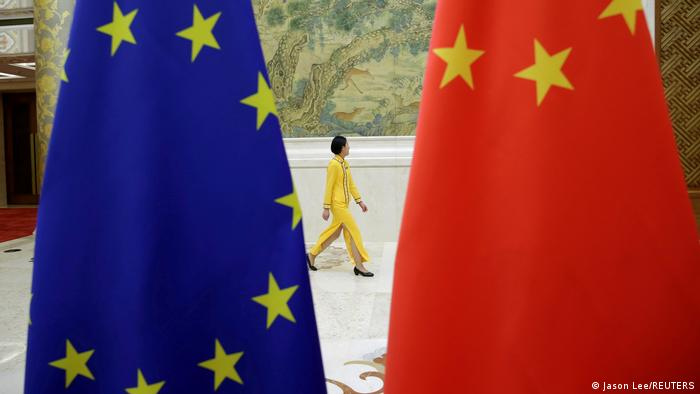 A woman walks past the flags of the EU and China in Beijing