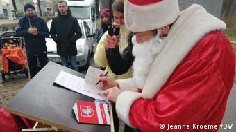 Человек в костюме Деда мороза выписывает паспорт