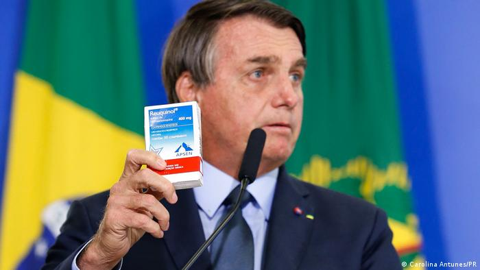 Bolsonaro, de terno e gravata, segura uma caixa de hidroxicloroquina. Ao fundo, desfocada, a bandeira do Brasil.