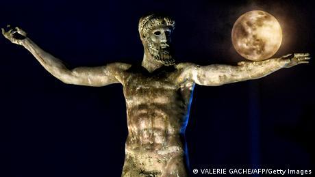 Poslednji pun mesec izgleda kao balon koji balansira na rukama ovog grčkog boga. Statua na obali grčkog grada Korinta je replika bronzane skulpture iz V veka pre nove ere. Original se nalazi u Arheološkom muzeju u Atini. Eksperti govore da se radi bogu mora Posejdonu - ili njegovom bratu Zevsu.