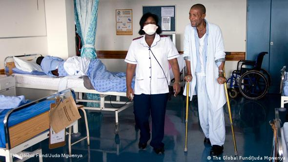 A TB patient walks around a ward at the King George V hospital in Durban, South Africa with the help of a nurse