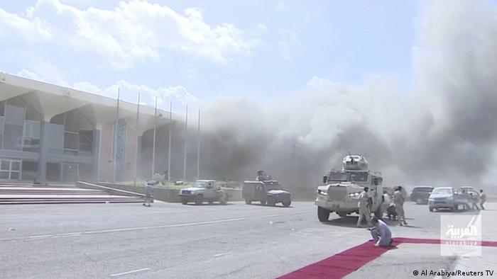 Dust from an explosion is strewn across an airport, in front of an airport building