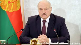 Александр Лукашенко сидит на фоне официального флага Беларуси