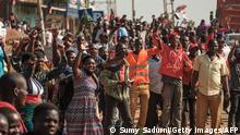 Supporters of Ugandan musician-turned-politician Robert Kyagulanyi, also known as Bobi Wine, welcome him on the streets as he sets off on his campaign trail towards eastern Uganda, near Kayunga, on December 1, 2020. - Bobi Wine is concluding his campaign rallies all over the country in preparation for the upcoming 2021 elections, where he will be challenging Ugandan President Yoweri Museveni, who has been in power for 35 years. (Photo by Sumy Sadurni / AFP) (Photo by SUMY SADURNI/AFP via Getty Images)