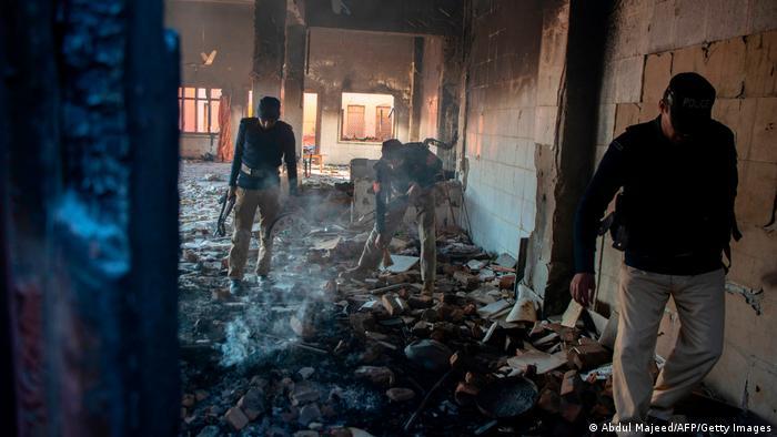 Polizisten inspizieren die ausgebrannte Ruine des Hindu Tempels in Karak