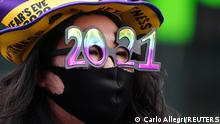 ARCHIV 21.12.2020 *** A woman wears '2021' numeral glasses in advance of New Year's eve in Times Square amid the coronavirus disease (COVID-19) pandemic in the Manhattan borough of New York City, New York, U.S., December 21, 2020. REUTERS/Carlo Allegri