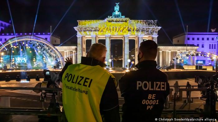 German police officers stand before Berlin's Brandenburg Gate on New Year's Eve