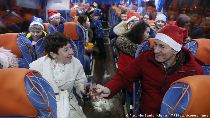 BdTD | Passagiere, von denen einige Moroz-Hüte (Santa Claus oder Father Frost) tragen, trinken in einem Partybus, der das neue Jahr feiert und am Freitag, dem 1. Januar 2021 durch Moskau, Russland, fährt