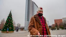 Passersby walk past Kosovo's government headquarters in Pristina on December 22, 2020. - Kosovo was preparing to call a snap poll, after its top court ruled last year's election of Prime Minister Avdullah Hoti was unconstitutional, delivering fresh upheaval to the democracy's crisis-hit politics. (Photo by Armend NIMANI / AFP) (Photo by ARMEND NIMANI/AFP via Getty Images)