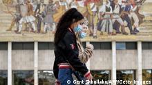Albanien Tirana | Coronakrise: Passanten mit Maske