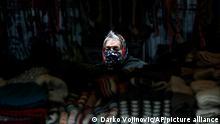 A street vendor wearing a face mask to protect against coronavirus waits in Belgrade's main pedestrian street, in Serbia, Thursday, Dec. 31, 2020. (AP Photo/Darko Vojinovic)