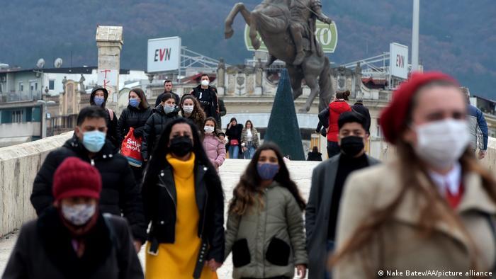 Menschen mit Masken laufen über einer Brücke auf den Betrachter zu, im Hintergrund ist die Statue eines Pferdes zusehen, vom Reiter sieht man nur die Beine und eine Hand