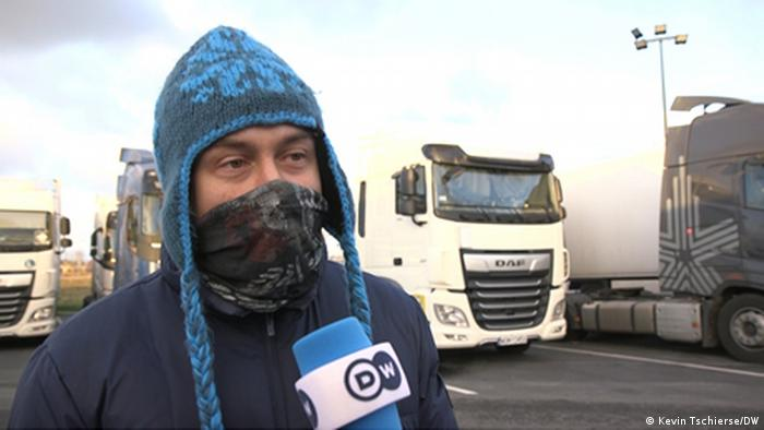 Yuri, a truck driver from Belarus, in a mask talking into a DW microphone