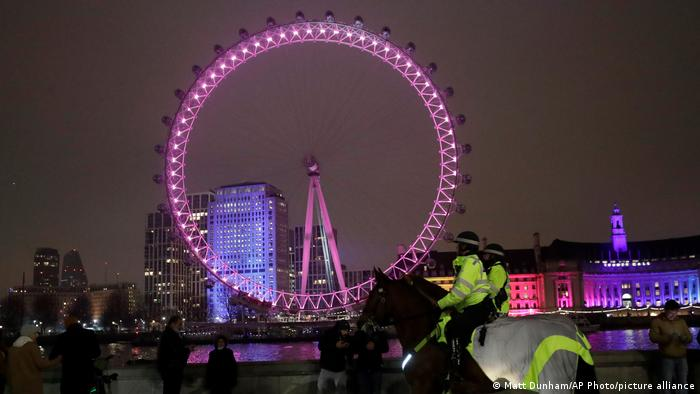 Mounted police officers ride along the Thames river across from the London Eye.