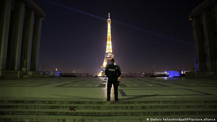 A lone police officer watches the Eiffel Tower alight on New Year's Eve