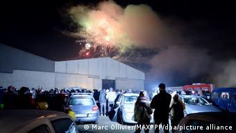 Люди, стоящие перед ангаром, где проходит рейв-вечеринка в Льероне