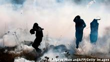 TOPSHOT - Palestinian demonstrators run from tear gas fired by Israeli troops, during a protest against Israeli settlements, in the village of Deir Jarir north of the occupied West Bank town of Ramallah, on January 1, 2021. (Photo by ABBAS MOMANI / AFP) (Photo by ABBAS MOMANI/AFP via Getty Images)