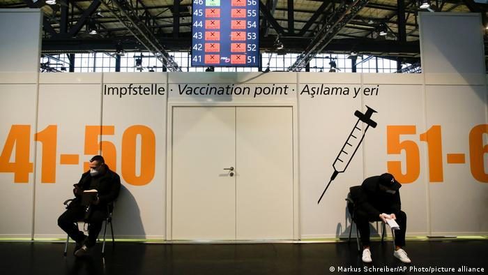 Two individuals sit outside a coronavirus vaccination center in Berlin