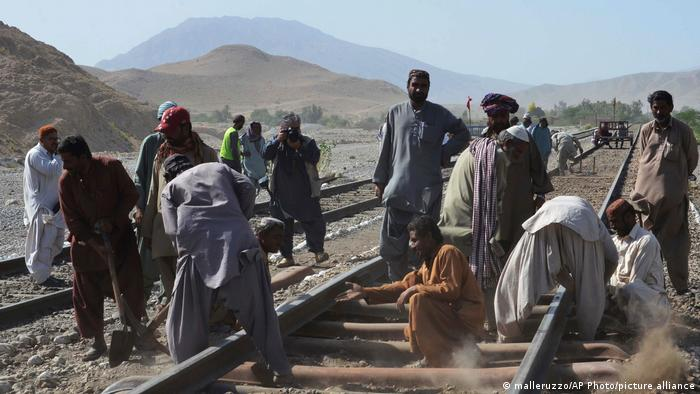 Pakistani railway staff repair a track damaged by a bomb blast in Mach in the Baluchistan province