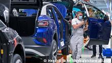 Ein Mitarbeiter im Volkswagenwerk in Zwickau komplettiert einen VW ID.4. Volkswagen produziert im Werk in Zwickau das erste reine Elektro-SUV. Hier läuft bereits der ID.3 vom Band. Von den bis 2025 jährlich geplanten 1,5 Millionen E-Fahrzeugen der Marke werden etwa 500.000 Einheiten für den ID.4 erwartet.