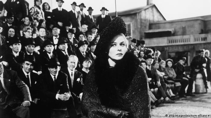 A woman dressed in black sits in front of a crowd