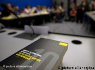 Schwarzes Buch mit grauer Zehn auf dem Titel liegt am dem Pressekonferenztisch (Foto: dpa)