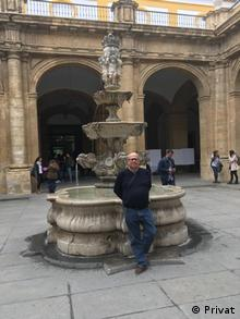 A picture of Andy Dore in front of a fountain situated on the plaza of a Spanish tourist resort