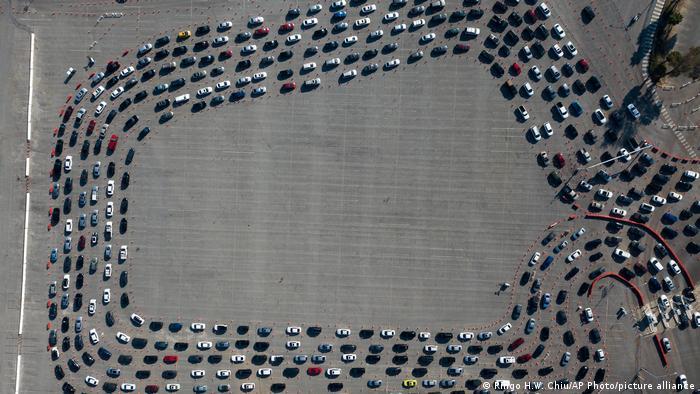 Šestostruki red automobila na parkingu jednog stadiona u Los Anđelesu. Ljudi u vozilima čekaju na testiranje na koronu.