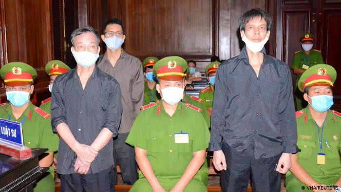 Pham Chi Dung (R), Le Huu Minh Tuan (C) and Nguyen Tuong Thuy (L) stand between police during their trial at a court in Ho Chi Minh city