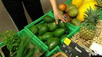 A hand reaching for an avocado in the supermarket