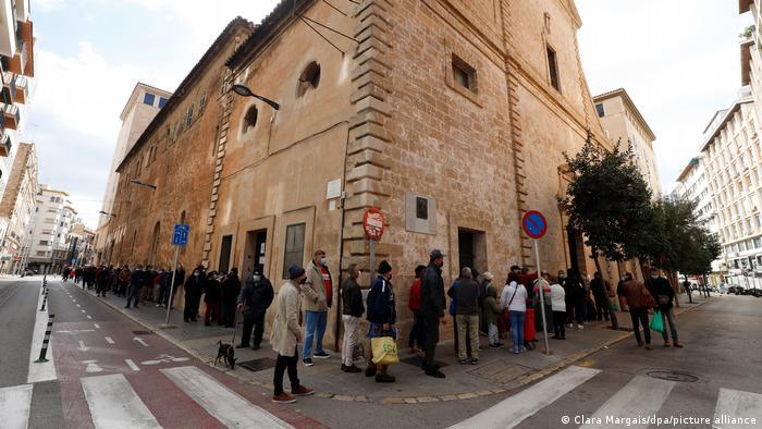 En Mallorca, personas haciendo fila para recibir ayuda con alimentos.