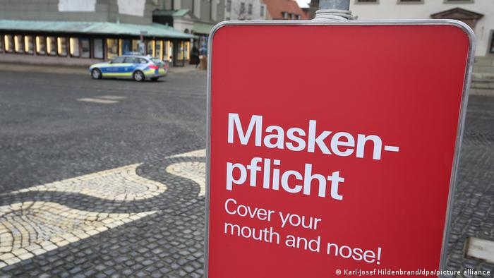 A sign on a street square telling people to cover mouth and nose