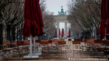 Abandoned cafe chairs and tables are seen on the deserted Unter den Linden boulevard leading up to landmark Brandenburg Gate in Berlin, Germany