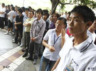 A group of company staff members stand at the Foxconn complex in the southern Chinese city of Shenzhen, Southern city in China, Wednesday, May 26, 2010. The head of the giant electronics company whose main facility in China has been battered by a string of worker suicides opened the plant's gates to scores of reporters Wednesday, hours after saying that intense media attention could make the situation worse. (AP Photo/Kin Cheung)