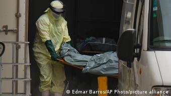 Медбрат грузит тело погибшего в машину