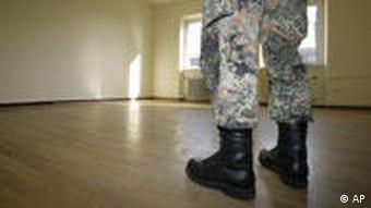 A man in fatigues stands in an empty room